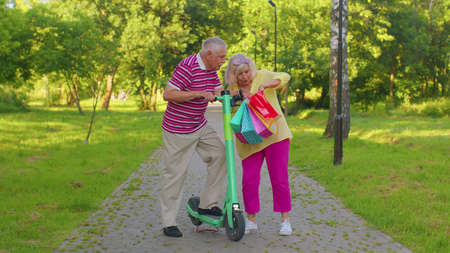 Elderly stylish couple tourists grandmother, grandfather walking after shopping in summer park with colorful bags and using electric scooter for riding. Senior man woman enjoying weekend time together