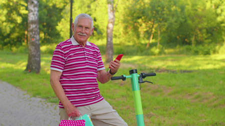 Caucasian old senior grandfather man leaning on electric scooter after shopping with colorful bags. Elderly gray-haired grandfather on vehicle outdoors holding smartphone. Pensioner grandpa in park