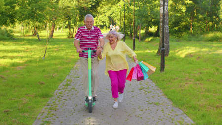 Elderly grandmother, grandfather enjoying weekend time together. Senior stylish couple tourists man woman walking in summer park with colorful bags after shopping and using electric scooter for riding 版權商用圖片