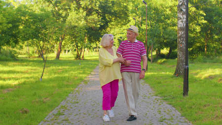 Senior stylish couple grandmother grandfather walking and talking in summer park. Happy old family husband, wife enjoying time together after retirement. Active elderly man pensioner walks with woman 版權商用圖片