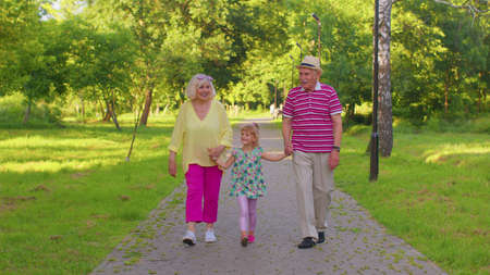 Child girl kid walking with senior grandmother and grandfather. Cute granddaughter holding hands with her grandparents man and woman in park. Happy family relationship. Active life after retirement