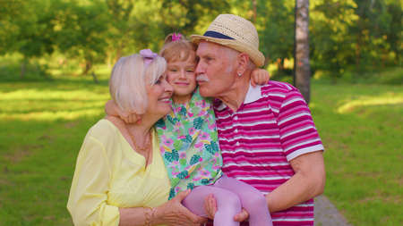 Child girl kid walking with senior grandmother, grandfather in park. Little smiling granddaughter kissing, embracing grandparents man and woman. Happy family relationship. Active life after retirement