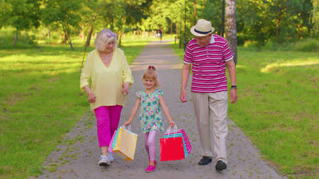 Child girl kid walking with senior grandmother grandfather with colorful bags after shopping. Granddaughter with retired grandparents man and woman enjoying weekend time together. Family relationship 版權商用圖片