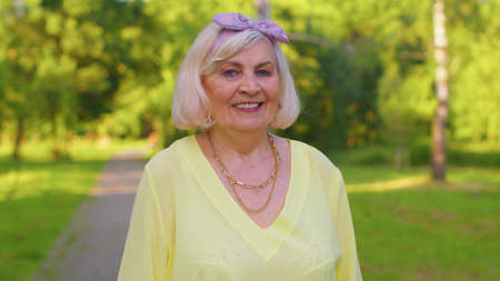 Cheerful lovely senior old gray-haired woman in casual yellow blouse posing isolated on summer park background. Active life after retirement. Elderly stylish smiling grandmother looking at camera
