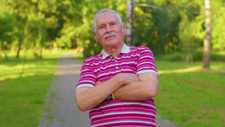 Happy stylish senior old gray-haired man in casual red t-shirt posing isolated on summer park background. Active life after retirement. Lovely elderly smiling grandfather pensioner looking at camera