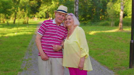 Portrait of senior stylish couple grandmother grandfather walking in summer park. Happy old family husband, wife enjoying time together after retirement. Active elderly man pensioner walks with woman 版權商用圖片