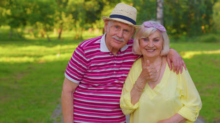 Portrait of senior old stylish tourists man and woman walking in summer park and embracing. Elderly grandmother grandfather enjoying date, traveling together. Active mature family after retirement
