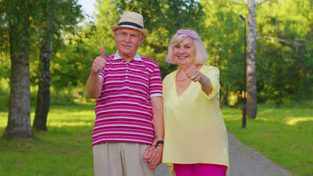 Senior stylish couple grandmother grandfather looking approvingly at camera showing thumbs up like sign positive something good. Happy elderly old family husband, wife walking in park after retirement