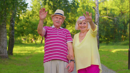 Senior stylish couple grandmother grandfather smiling friendly at camera, waving hands gesturing hello or goodbye, welcoming with hospitable expression. Happy old family husband, wife after retirement
