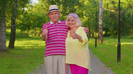 Happy senior couple grandmother grandfather looking approvingly at camera showing thumbs up like sign positive something good. Stylish elderly old family man and woman walking in park after retirement