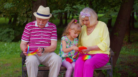 Senior stylish old couple grandmother grandfather with granddaughter child squeezing presses anti-stress push pop it popular toy in park. Family with sensory game with buttons. Trendy fidgeting game 版權商用圖片