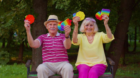 Smiling stylish senior grandmother grandfather holding squeezing anti-stress silicone toy simple dimple game in park. Man woman holding popular  bubble squishy game with buttons. Stress reliever 版權商用圖片
