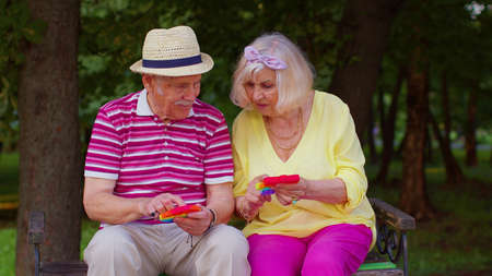 Senior stylish couple grandmother grandfather squeezing presses colorful anti-stress push pop it popular toy in park. Old mature family play trendy fidgeting sensory game with buttons. Stress reliever