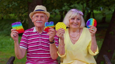 Smiling senior old grandmother grandfather holding anti-stress touch screen push  popular toy. Grandparents with sensory game with buttons. Trendy fidgeting game for stressed children and adults