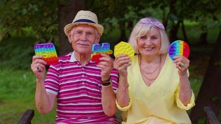Senior stylish couple grandmother grandfather showing squeezing colorful anti-stress push pop it popular toy in park. Old elderly family play trendy fidgeting sensory game with buttons. Thumbs up