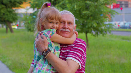 Little smiling granddaughter kissing, embracing grandparent man. Portrait of child girl kid walking with senior stylish old grandfather in park. Happy family relationship. Active life after retirement