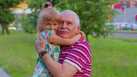 Happy family relationship. child girl kid walking with senior stylish old grandfather in park. Portrait of little smiling granddaughter hugging, embracing grandparent man. Active life after retirement 版權商用圖片