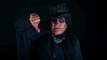 Sinister senior old mature man in costume of Halloween witcher showing thumbs down sign gesture, expressing discontent disapproval, dissatisfied, dislike. Horror theme of cosplay clown, vampire, beast Standard-Bild