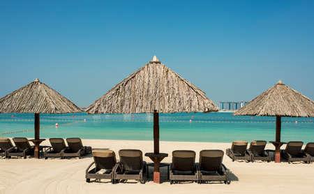 Beach sunbeds and cabanas on the sand, sea view, luxury beach holidays