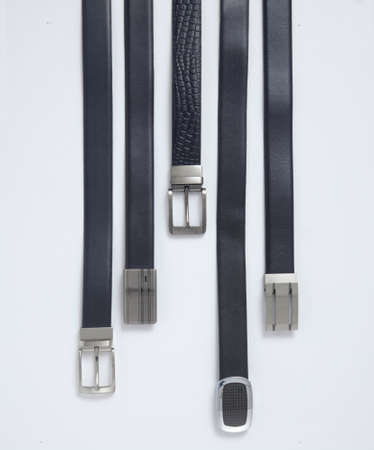 Bunch of men's belts, group of leather belts for man, isolated. View of different leather belts with buckles.