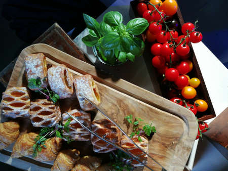 Cherry tomatoes and oregano leaves with pastry on a wooden board. Breakfast pastry with cherry tomatoes and basil from above. Variety of homemade bagels sandwiches with sesame and poppy seed.