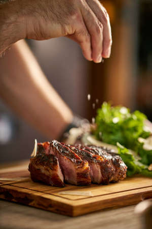 Chef's hand putting salt on a steak, cut meat on a wooden board.