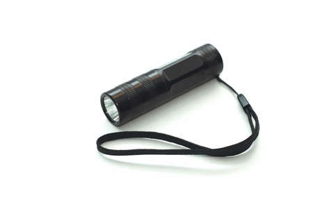 Small black flashlight on white