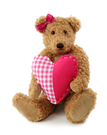 Teddy bear with red heart isolated on white background photo
