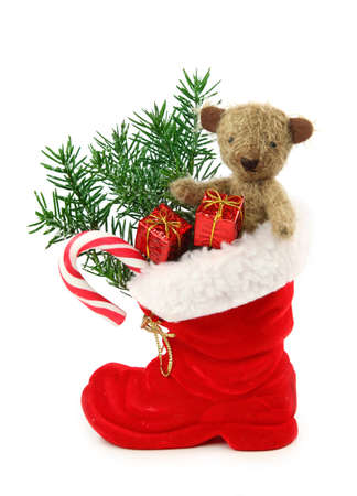 Red christmas boot with gift boxes and teddy bear isolated on white background photo
