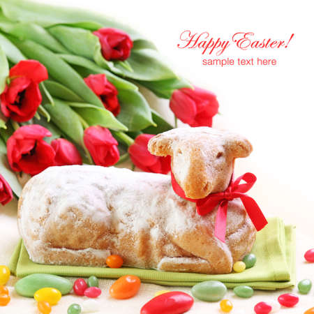 Easter lamb cake and red tulips on white background photo