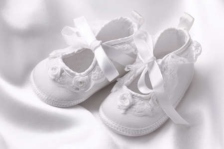 White baby booties on white silk Stock Photo - 9330762