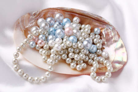 Pearls in a shell on a white silk photo