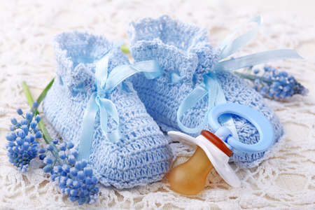 Handmade blue baby booties with dummy and flowers photo