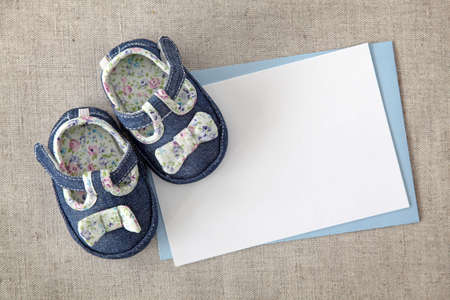 Baby shoes and blank note on textile background photo