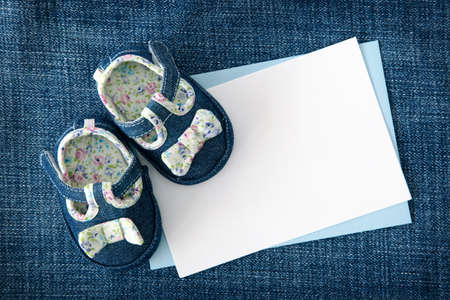 Baby shoes and blank note on blue background photo
