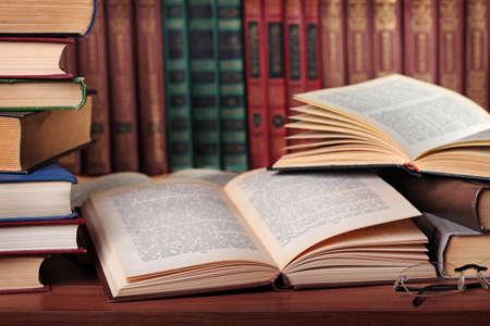 libros abiertos: Pila de libros con gafas de lectura en el escritorio