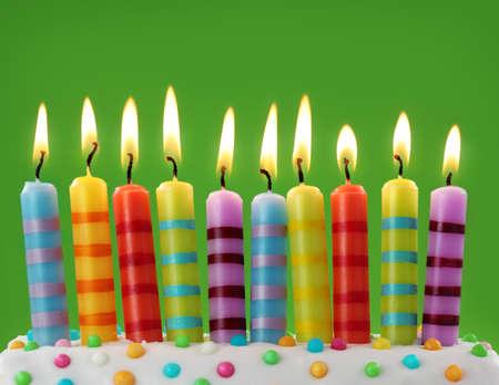 torta con candeline: Dieci candeline colorate su sfondo verde Archivio Fotografico