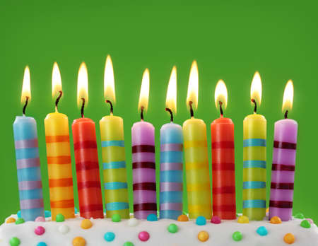 the birth: Ten colorful candles on green background