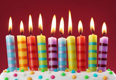 birthday food: Ten colorful candles on red background  Stock Photo