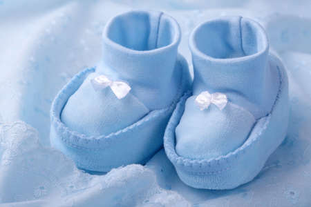 christening: Blue baby booties on blue background Stock Photo