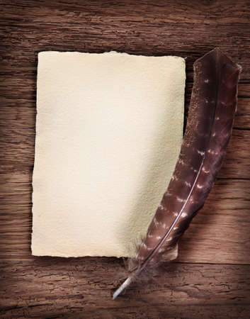 Old parchment and quill pen on wooden background photo