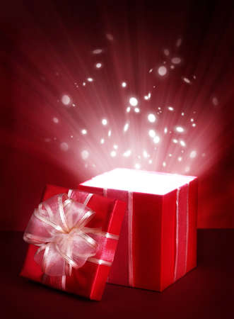 Open magic gift box on red background photo
