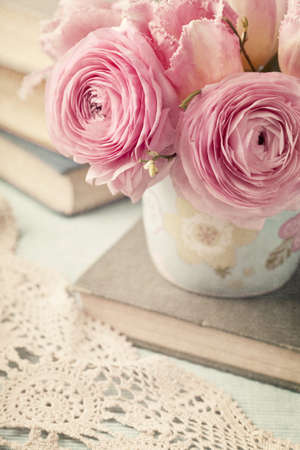 antique vase: Pink flowers and old books Stock Photo