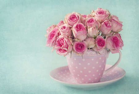 antique vase: Pink roses in a cup on blue background