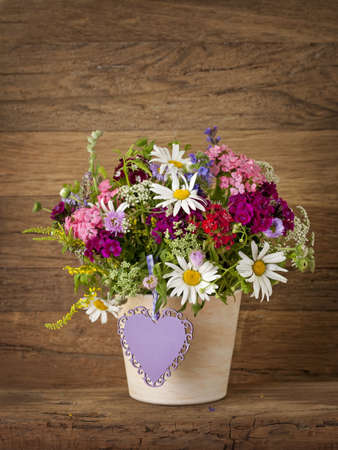 Summer flowers in vase on wooden background photo