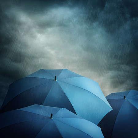 lluvia paraguas: Oscuras nubes de tormenta y sombrillas