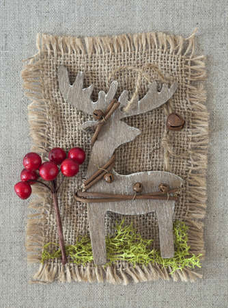 Wooden christmas deer on fabric background photo