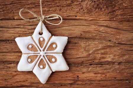 Gingerbread sneeuwvlok opknoping over houten achtergrond Stockfoto