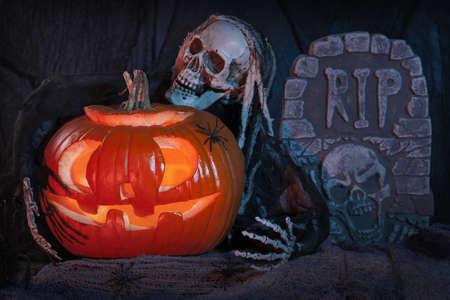 spooky graveyard: Skull monster and halloween pumpkin decoration
