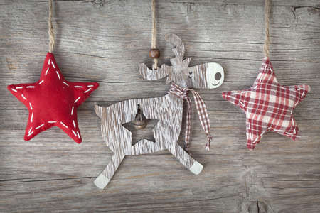 Wooden christmas deer and red stars on wooden background Reklamní fotografie